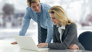 Woman and man in front of a laptop