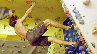 a climber hanging head down from a climbing wall