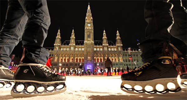 skates, in the background Vienna City Hall at night