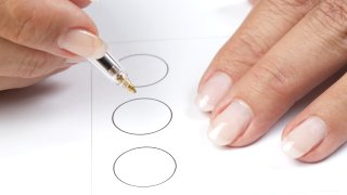 Hands of a woman filling out a ballot