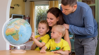 Parents look at a globe with two boys