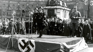 Heinrich Himmler standing on a podium holding a speech