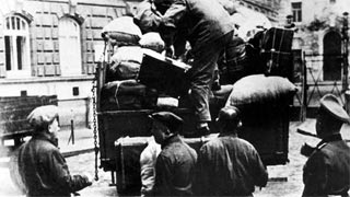 A member of the SS oversees the loading of the luggage of Viennese Jews singled out for deportation