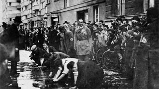To the acclaim of numerous bystanders, Jews are forced to wash the roads