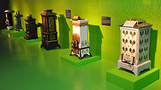 Several stoves in a row, displayed in a green exhibition room.