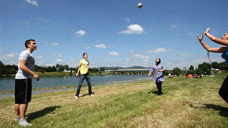 Four people playing volleyball on a meadow next to the water.