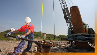 Mitarbeiter der Deponie bei der Arbeit an einem Gasbrunnen