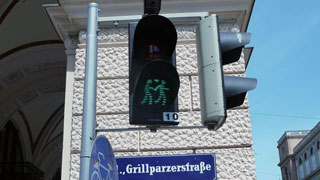 Green pedestrian traffic lights displaying two men who hold hands, a heart as symbol between them