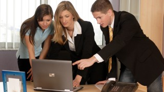 Two women and a man looking on a laptop
